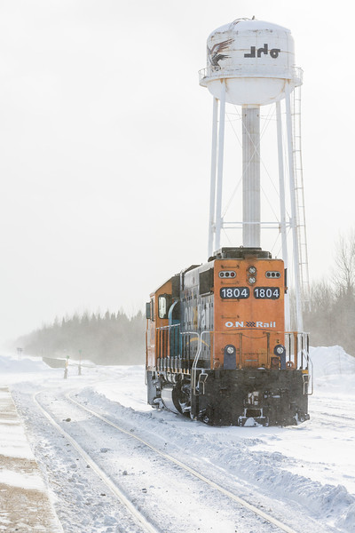 GP38-2 1804 in Moosonee Station in freight service. Shot from narrow end, showing Moosonee's disused water tower, shot into the sun.
