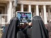 Two nuns looking at Pope Benedict on a large TV screen outside St Peters Basilica in Rome, Italy
