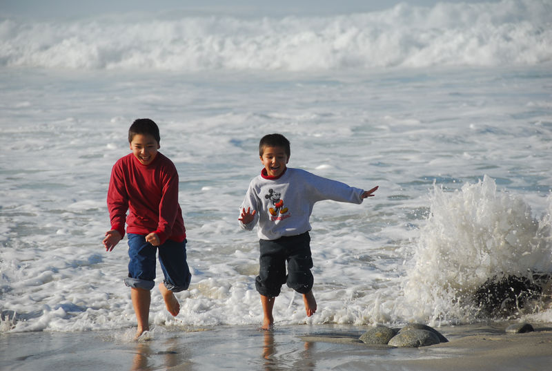Austin and Ethan running from the waves.