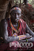 Close up portrait of Masai warrior in plaid red and black shuka, beaded jewellery, sitting inside enkang enclosure, Masai village, Kenya, Africa