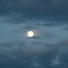 A full moon showing through the clouds even when it is still daylight at 9:00 at night in the summer hours of Alaska.