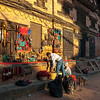 A stallholder sets out his wares in a beam of early morning sunlight. Bhaktapur. Nepal