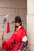 SEOUL, KOREA - April 27, 2012: An unidentified Korean guard dressed in red uniform and holding a lance stands motionless at the entrance to the Gyeongbokgung Palace in Seoul on April 27, 2012.