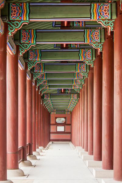 A colonnade at the Geunjeongmun Gate (or third gate) of the Gyeongbokgung Palace complex in Seoul, Korea shows the row of red columns topped by ornately painted wood beams.