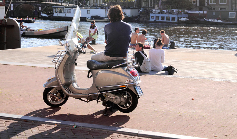 People relaxing by River Amstel Amsterdam Holland