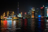 A lighted ship at night, wth the Pŭdōng New Area Shànghǎi Skyline behind it, from the Bund.