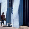 Woman walking past blue wall, Calle Pio Rosado, Santiago de Cuba, Cuba