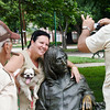 The 'keeper of the glasses' (left) stands by as a tourist and her dog pose for their picture with a statue of John Lennon in John Lennon Park in Havana.  The keeper maintains possession of Lennon's signature round glasses.  He puts them on the statue as tourists pose with the legend, and immediately takes them off and deposits them in his pocket after the pictures are taken. He stands guard sitting at a nearby park bench.