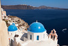 Classic view of blue-painted domes on Orthodox Greek churches in the town of Oia on the island of Santorini in the Greek Islands. The town of Thera is in along the island rim in the background.
