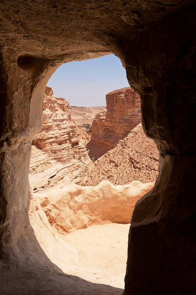 The valley of the Ein Avdat park in the Negev Desert in Israel is framed through an opening to one of the caves in the canyon walls.