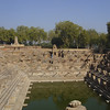 View of north edge of tank with person looking at small shrine in previous photo- Sun Temple, Modhera Gujurat India