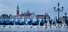 Aqua Alta: view of San Marco basin, looking past moored gondolas with motion blur of rough water and flooding in foreground, to San Giorgio Maggiore church and nearby harbour, autumn  in Venice, Northern Italy