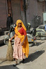 Sweeper lady in bright coloured clothing cleaning the streets of Jaipur. Street view of Jaipur, Rajasthan, India.