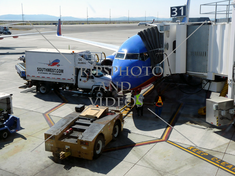 Parked airplane being serviced at Ontario Airport in California.