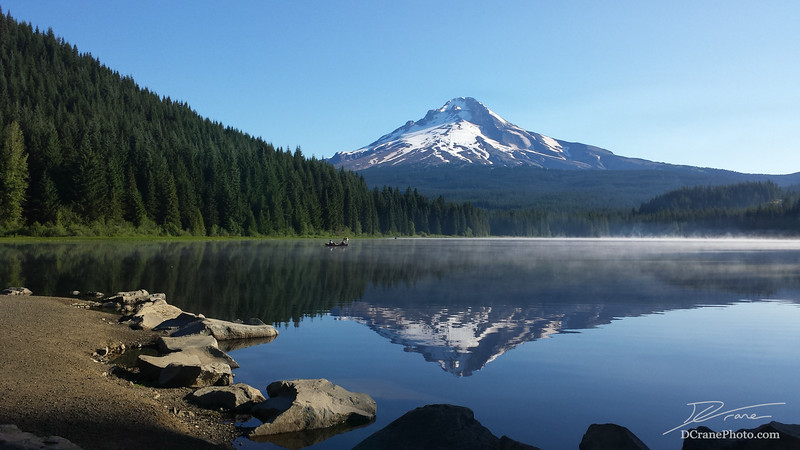 Mount Hood reflected in Trillium Lake as two fisherman paddle across the water in a canoe. Part of the trail across the dam, also frequented by fisherman,  can be seen in the bottom corner.