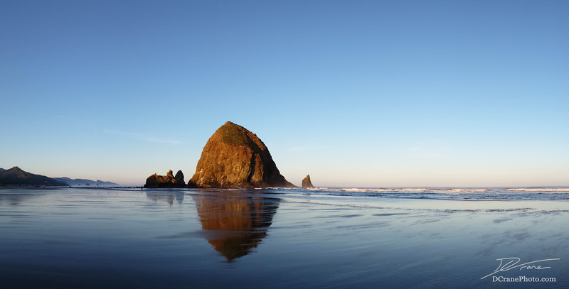 First light on Haystack Rock just after sunrise on a cool summer morning. The sea stack - a name given to rock or island that was once a part of, but now eroded from the mainland - is reflected in the wet sand on Cannon Beach as the tide recedes.