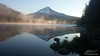 Sunrise on Mount Hood reflected in Trillium Lake in the early morning light with a light fog.