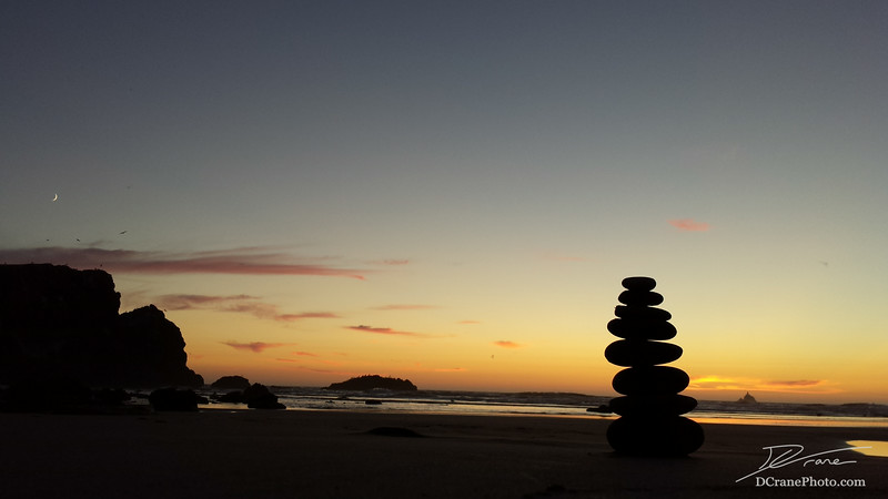 Silhouette of a cairn on Crescent Beach in Ecola State Park, Oregon. The Crescent Moon and several sea stacks are also visible.