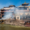 Smoke from cremations obscure Pashupatinath Temple (400AD) and burning ghats on the banks of the Bagmati river, Kathmandu.  It is regarded as one of the most sacred among the temples of Shiva (Pashupati) in the world.  Entrance by non-Hindus is verboten.