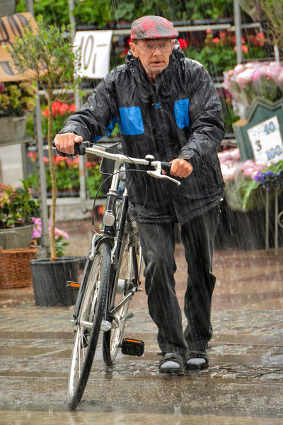 Man Walking Bicycle in the Rain