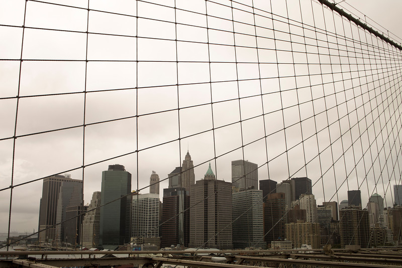 A view of Manhattan downtown and the skyscrapers near Wall Street from the Brooklyn Bridge. The gloomy sky with leaden gray clouds is segmented by a web of cables from the suspension bridge.