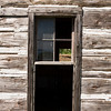 A window on an old, weathered barn that is surrounded by rough-hewn wood planks. There is a view through some missing glass to the other side. Note the building (and window frame) has gone slightly askew over the years.