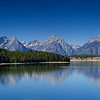 Panoramic landscape of the reflections of the Teton peaks on Jackson Lake.