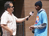 Young African-American man being interviwed by Telemundo, TV reporter with microphone.