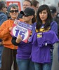 "Woman wearing SEIU t-shirt holding sign ""Justice For Janitors, Fight For 15"", next to her young woman wearing SEIU t-shirt, and woman wearing sunglasses."