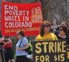 "Woman holding ""strike for $15"" sign"" at minimum wage protest, large banner about poverty wages behind her."