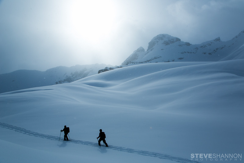 Backcountry skiers hike through fresh powder snow with Mount Kemmel in the background near Icefall Lodge in the Canadian Rockies.<br /> Athletes: Oleh Antonyshyn & Andy Adamson<br /> Location: Icefall Lodge, BC