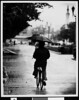 Student riding a bike in the rain,  USC, 1977
