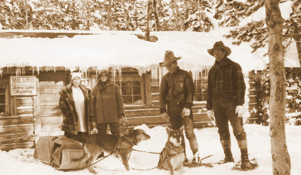 Geraldine Lucas, 2nd from left, about 1926 at the Post Office at Jenny Lake about 3 miles north of her homestead. She traveled that day with her dogsled team. At far left is Mrs. Albert (Lida) Gabbey who was postmistress that year. [Lida and her husband began operating the Square G guest ranch, northeast of Jenny Lake between 1927 and 1931, until they sold out in 1951 to the Jackson Hole Preserve.] 2nd from right is Leonard Timmermeyer; at right is Tony Grace, a local cowboy who owned and operated the Danny Ranch during the 1920s. That ranch is now the heart of Jenny Lake Lodge.<br /> <br /> Geraldine was a strong and independent woman, and when John D. Rockefeller's Snake River Land Company began buying up property in the Hole in the late 1920s and '30s, she refused to sell out. Harold Fabian, a vice-president of the land company, made many entreaties to her to no avail. She was considered a 'tough nut', and was a thorn in the side of Rockefeller and Fabian for many years.
