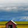 Small red barn and stormy sky