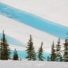 Bright blue water appearing in a reservoir during snow melt on Whistler Mountain<br /> Stock video footage by Mitch Winton - coastphoto.com