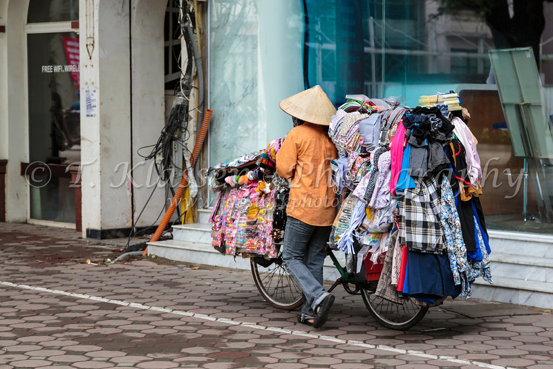 A street vendor selling goods from her bicycle in Hanoi, Vietnam, Asia.