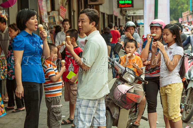 Eating ice cream on the street in downtown Hanoi, Vietnam, Asia.