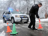 A  North Wales Borough Police Officer replaces traffic cones along Prospect Ave after a large tree fell onto a residence taking down power lines on Wednesday afternoon February 5,2014. Photo by Mark C Psoras/The Reporter