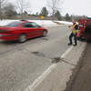 Record-Eagle/Keith King<br /> Tyson Baynton, left, and Jeff Hall, with the Grand Traverse County Road Commission, wait for a car to pass before repairing potholes on M-186 in Fife Lake Township.