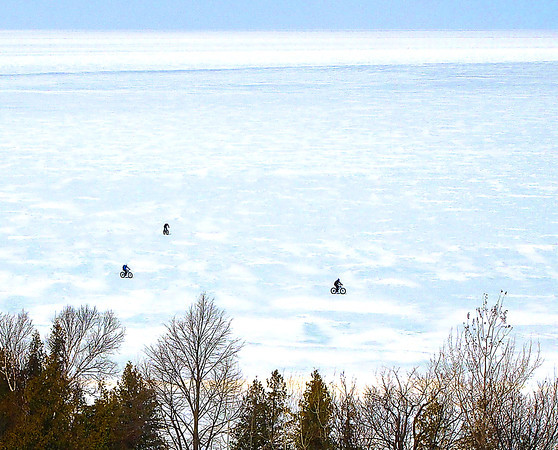 Record-Eagle/Dan Nielsen A trio of bicyclists venture a short way out on the ice of Little Traverse Bay near Petoskey on Sunday, April 6, 2014.