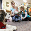 Record-Eagle/Keith King  Kaia Beebe, from right, 8, of Interlochen, reads alongside Alanna Beebe, 22 months, and her mother, Nicole Beebe, as Katie, a registered therapy dog, a St. Bernard, lies near Wednesday, October 24, 2012 at the Interlochen Public Library.