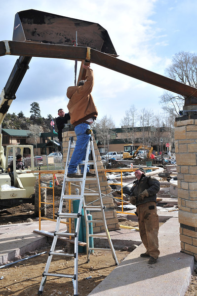 Worker align a metal beam of the arch in Bond Park on Thursday. The arch will welcom visitors to the newley remodeled park.