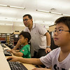 Two boys use the computer at WMC, while their father watches.<br /> <br /> Taken on July 4, 2014 by James Cadden.