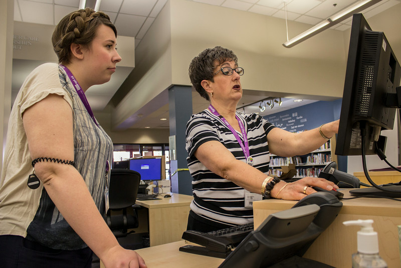 EPL Library Assistants, (L-R) Sally Scott and Kelly Stent troubleshoot on a computer.<br /> <br /> Taken on July 4, 2014 by James Cadden.