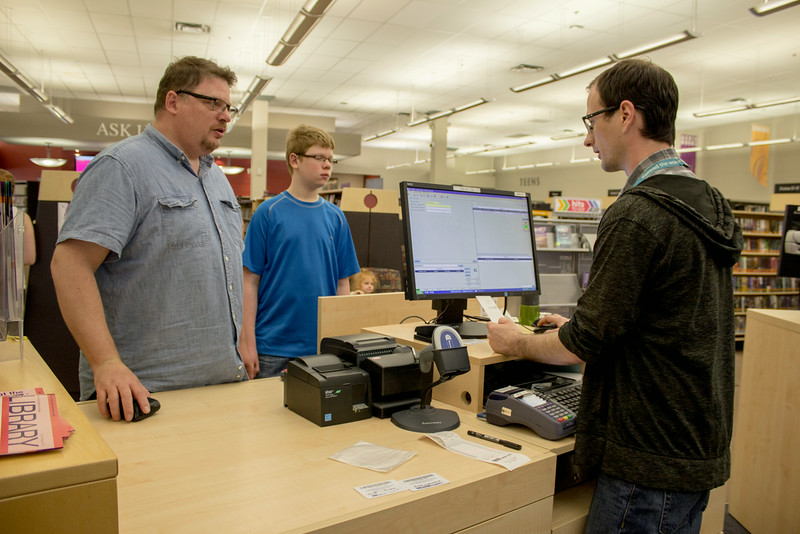 EPL Customers, Mike Lawrence and his son, receive customer service from EPL Library Assistant, Tyson Dobko.<br /> <br /> Taken on July 4, 2014 by James Cadden.