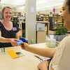 EPL Library Assistant, Donna Bateman, hands a woman her new library card.<br /> <br /> Taken on July 4, 2014 by James Cadden.
