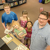 EPL Customer, Mike Lawrence, and his band of children, sign out books using the self checkout machine.<br /> <br /> Taken on July 4, 2014 by James Cadden.