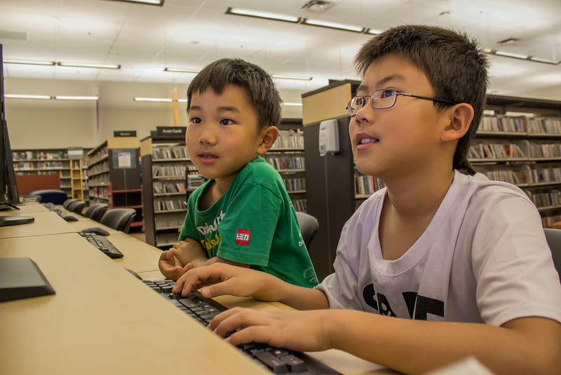 Two boys use the computer at WMC.<br /> <br /> Taken on July 4, 2014 by James Cadden.