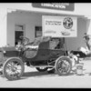 Old REO car with streamline poster on it, with colored boys & at station, Southern California, 1934