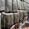 CUZCO. PUNO LADY WALKS ALONG AN INCA WALL.